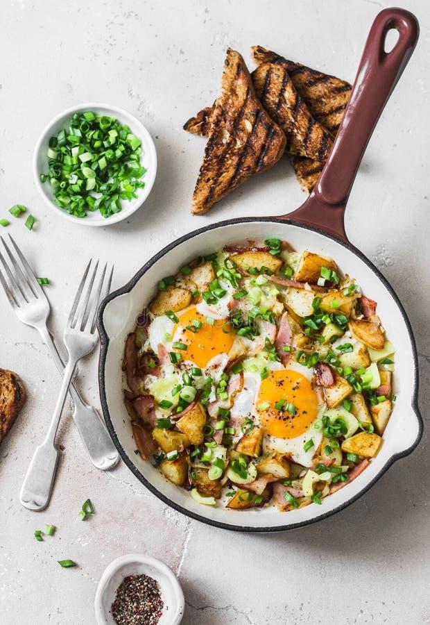Πατάτες, ζαμπόν, hash προγευμάτων αυγών σε ένα τηγανίζοντας τηγάνι σε ένα ελαφρύ υπόβαθρο, τοπ άποψη Εύγευστο, θρεπτικό πρόγευμα, στοκ φωτογραφία