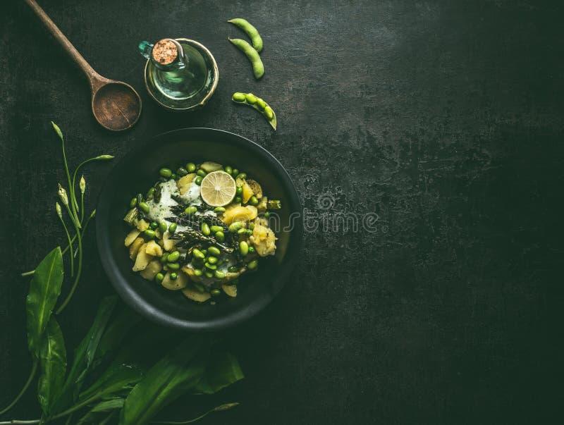 Πατάτες και πράσινη σαλάτα σπαραγγιού με τη σόγια edamame και ramson γιαούρτι που ντύνει στο μαύρο κύπελλο στο σκοτεινό αγροτικό  στοκ φωτογραφία με δικαίωμα ελεύθερης χρήσης