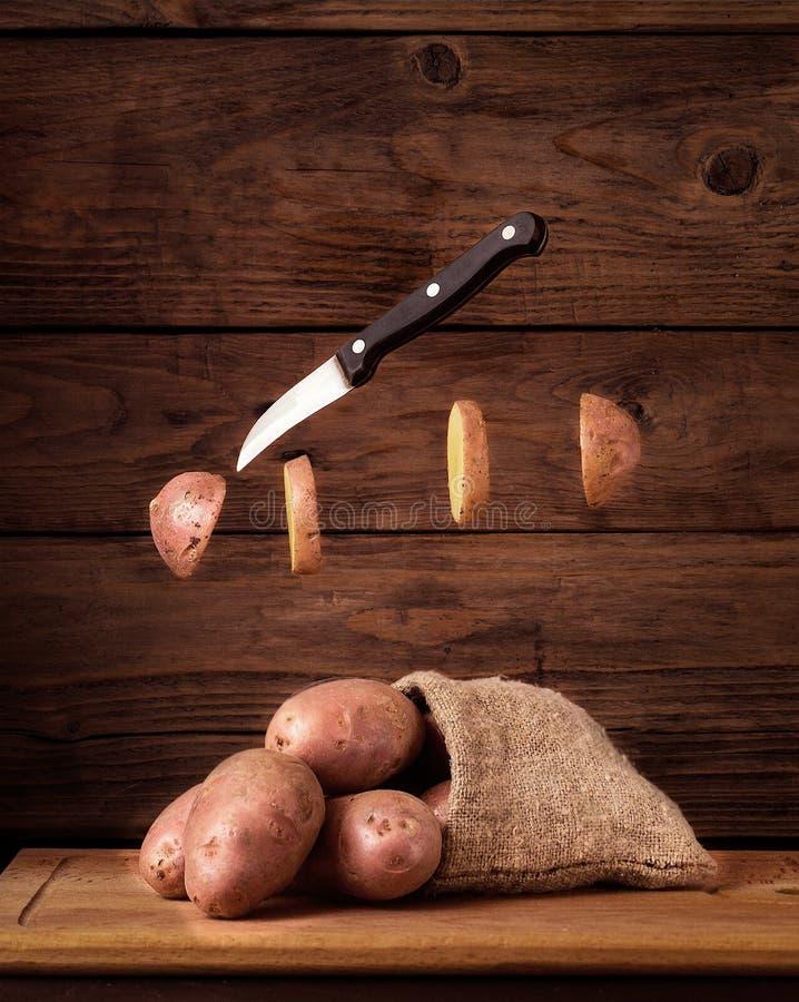 Πατάτες με τις φέτες και το μαχαίρι levitate στοκ φωτογραφίες
