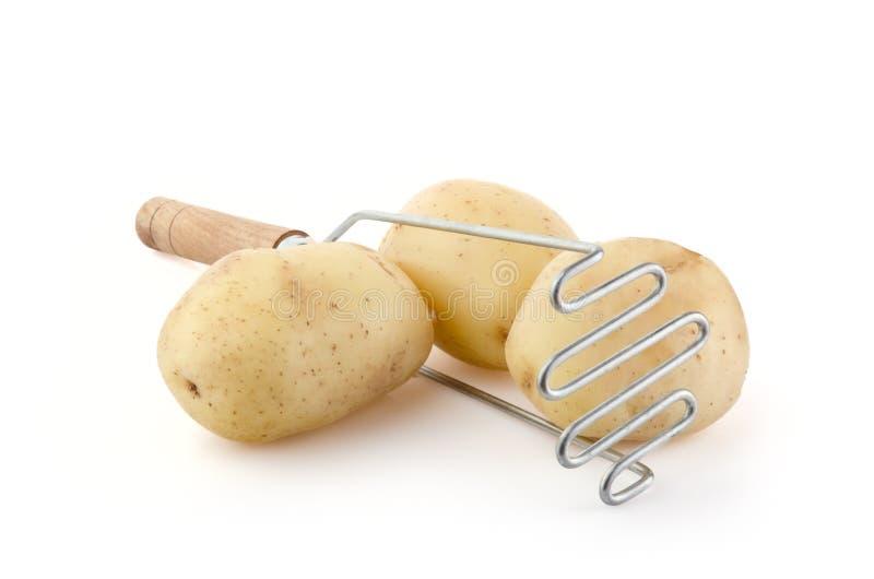 Πατάτες με Masher πατατών στο λευκό στοκ φωτογραφίες