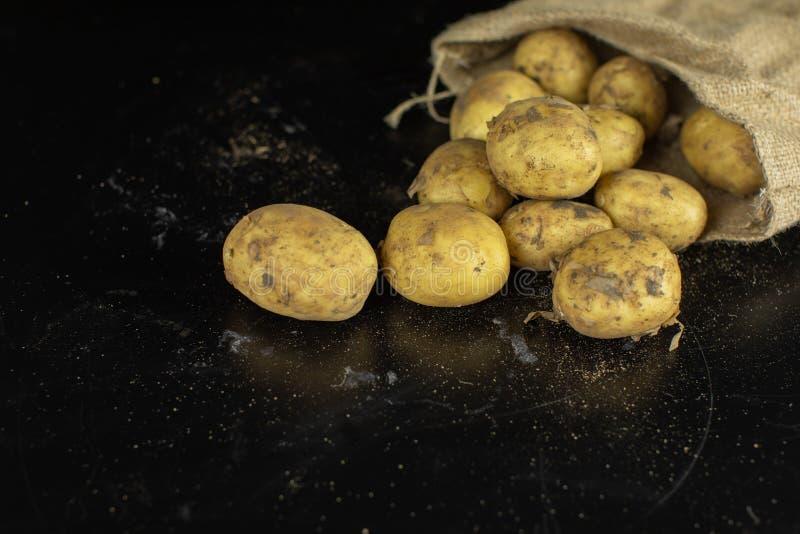 Πατάτες στο μαύρο surfase σε μια τσάντα καμβά Φρέσκια βρώμικη ακατέργαστη πατάτα σε έναν σωρό στοκ εικόνα
