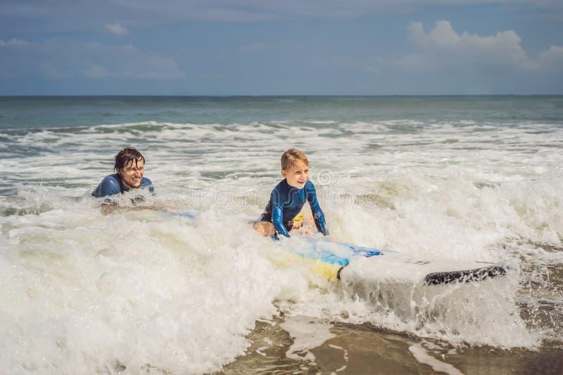 Πατέρας ή εκπαιδευτικός που διδάσκει το 5χρονο γιο του πώς να κάνει σερφ στη θάλασσα στις διακοπές ή τις διακοπές Ταξίδι και αθλη στοκ εικόνα