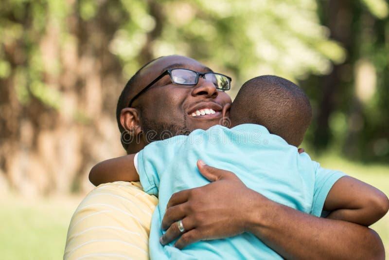 Πατέρας αφροαμερικάνων που αγκαλιάζει το γιο του στοκ φωτογραφίες