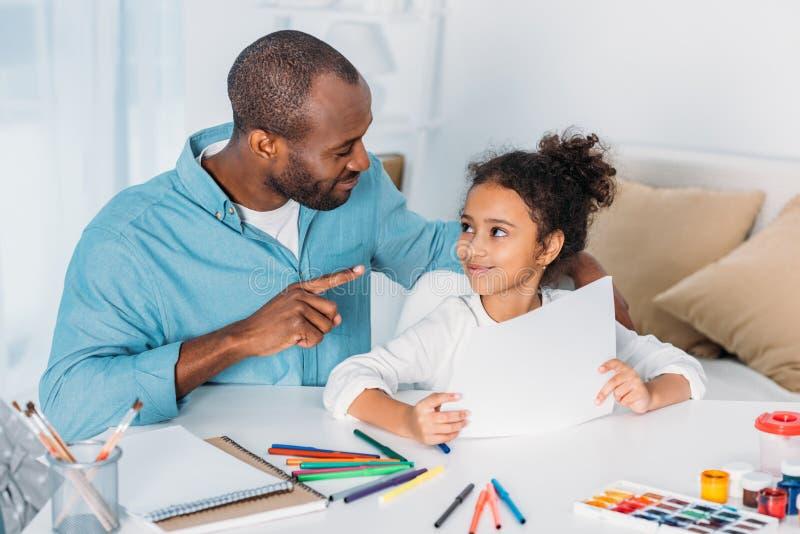 πατέρας αφροαμερικάνων που δείχνει σε κάτι και που εξετάζει την κόρη στοκ εικόνα