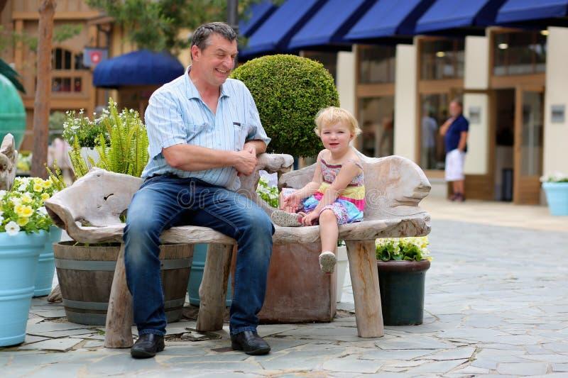 Πατέρας και λίγη κόρη που χαλαρώνουν στην πόλη στοκ εικόνες