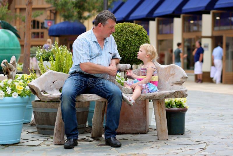 Πατέρας και λίγη κόρη που χαλαρώνουν στην πόλη στοκ φωτογραφίες