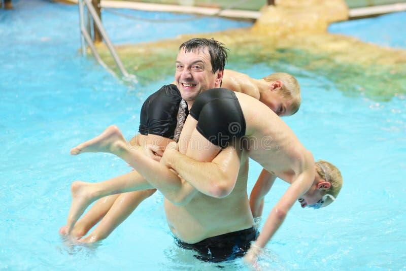 Πατέρας και γιοι που έχουν τη διασκέδαση στην πισίνα στοκ φωτογραφία με δικαίωμα ελεύθερης χρήσης