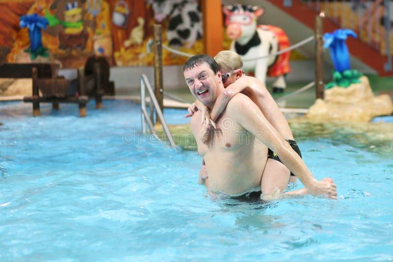 Πατέρας και γιοι που έχουν τη διασκέδαση στην πισίνα στοκ εικόνα με δικαίωμα ελεύθερης χρήσης