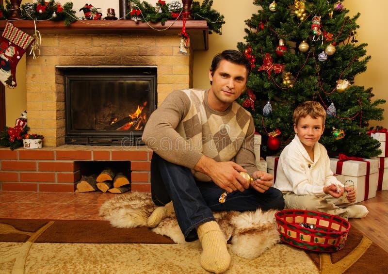 Πατέρας και γιος κοντά στην εστία στο σπίτι Χριστουγέννων στοκ φωτογραφίες με δικαίωμα ελεύθερης χρήσης