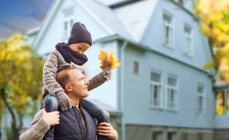 Πατέρας και γιος με τα φύλλα σφενδάμου φθινοπώρου πέρα από το σπίτι στοκ εικόνα
