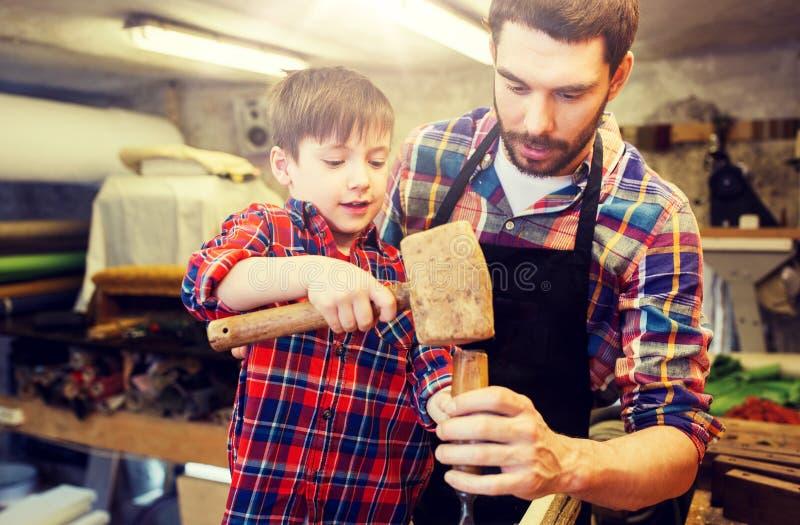 Πατέρας και γιος με τη σμίλη που λειτουργεί στο εργαστήριο στοκ φωτογραφίες
