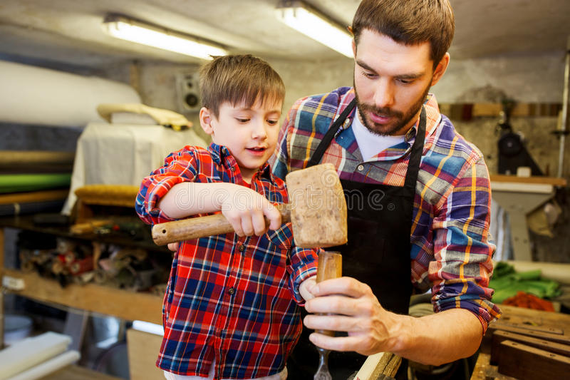 Πατέρας και γιος με τη σμίλη που λειτουργεί στο εργαστήριο στοκ εικόνες με δικαίωμα ελεύθερης χρήσης