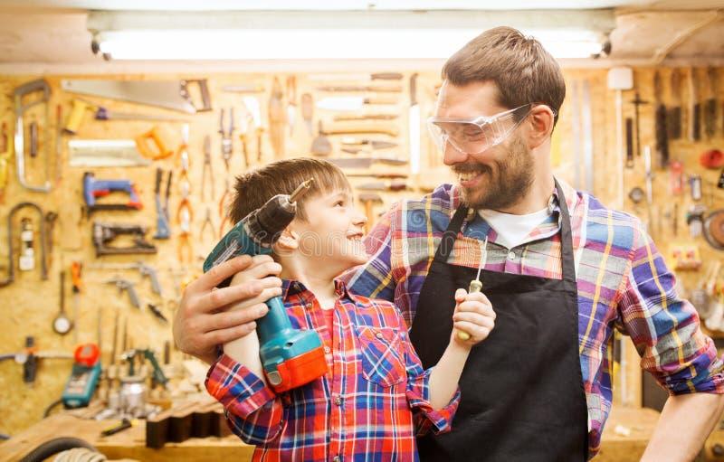 Πατέρας και γιος με το τρυπάνι που λειτουργεί στο εργαστήριο στοκ εικόνες