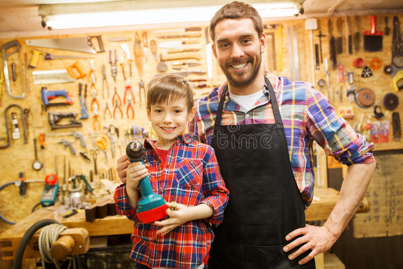 Πατέρας και γιος με το τρυπάνι που λειτουργεί στο εργαστήριο στοκ φωτογραφίες