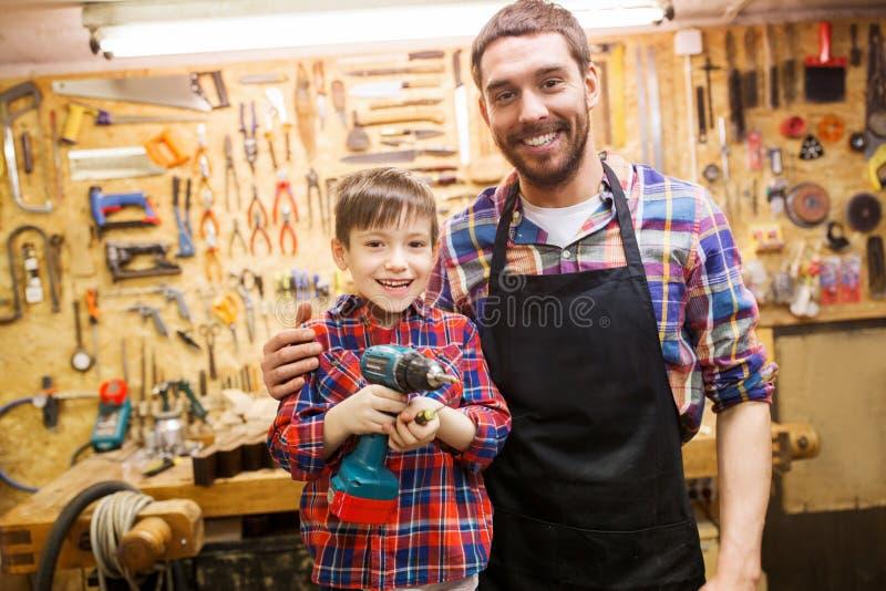 Πατέρας και γιος με το τρυπάνι που λειτουργεί στο εργαστήριο στοκ φωτογραφία με δικαίωμα ελεύθερης χρήσης