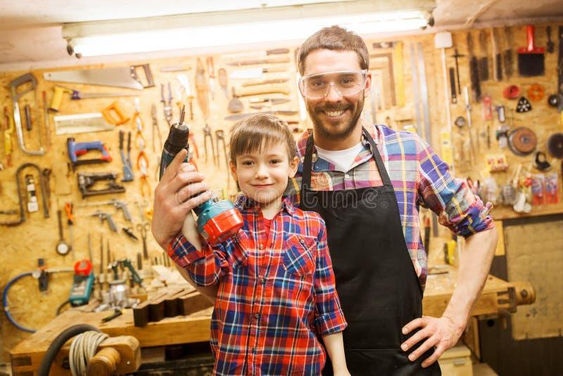 Πατέρας και γιος με το τρυπάνι που λειτουργεί στο εργαστήριο στοκ εικόνα με δικαίωμα ελεύθερης χρήσης