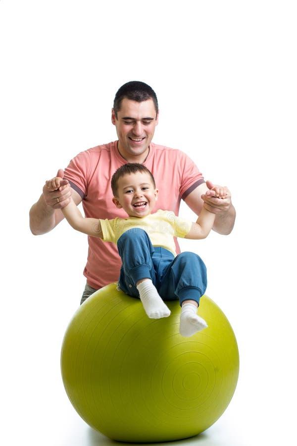 Πατέρας και γιος παιδιών που έχουν τη διασκέδαση με τη γυμναστική σφαίρα στοκ εικόνα