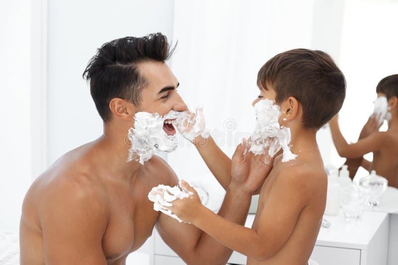 Πατέρας και γιος που έχουν τη διασκέδαση εφαρμόζοντας τον αφρό ξυρίσματος στοκ εικόνα με δικαίωμα ελεύθερης χρήσης