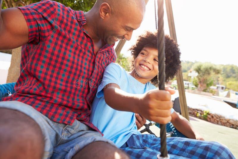 Πατέρας και γιος που έχουν τη διασκέδαση στην ταλάντευση στην παιδική χαρά στοκ εικόνες