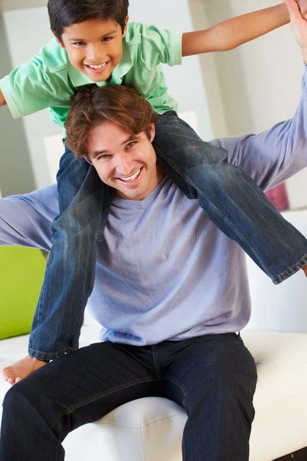 Πατέρας και γιος που έχουν τη διασκέδαση στον καναπέ από κοινού στοκ εικόνα