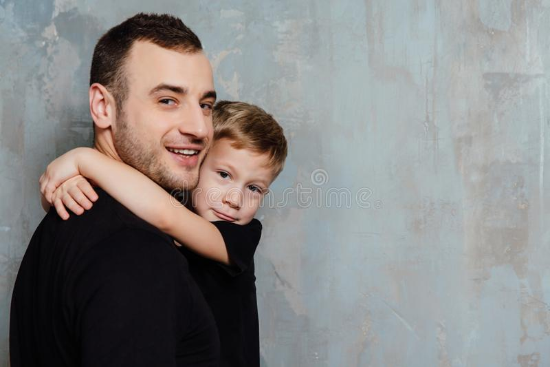 Πατέρας και γιος που αγκαλιάζουν το γιο στο γκρίζο υπόβαθρο τοίχων Άτομο και αγόρι μόδας στα μαύρα ενδύματα στοκ εικόνα