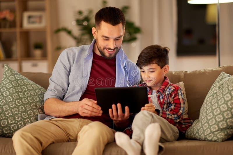 Πατέρας και γιος που ακούνε τη μουσική στο PC ταμπλετών στοκ εικόνα με δικαίωμα ελεύθερης χρήσης