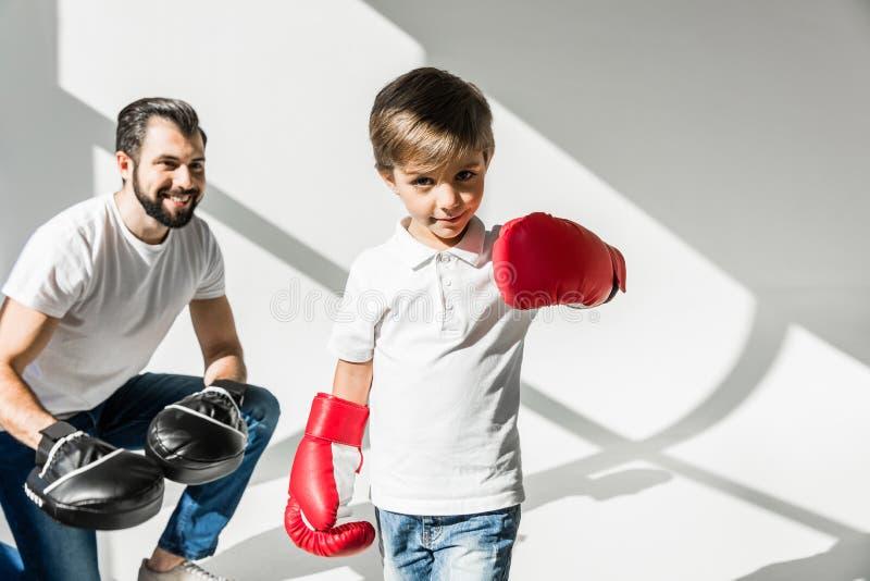 Πατέρας και γιος που εγκιβωτίζουν από κοινού στοκ φωτογραφία