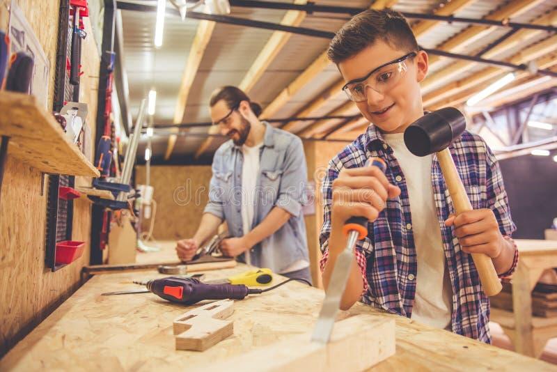 Πατέρας και γιος που εργάζονται με το ξύλο στοκ εικόνα