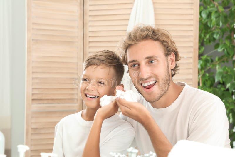 Πατέρας και γιος που εφαρμόζουν τον αφρό ξυρίσματος στοκ φωτογραφία με δικαίωμα ελεύθερης χρήσης