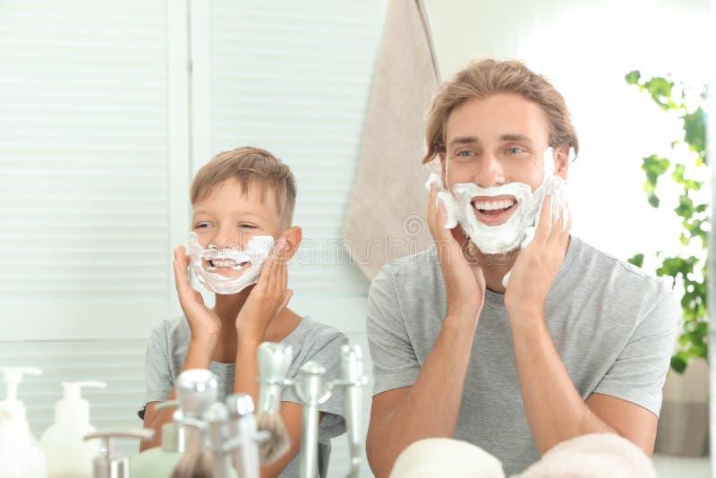 Πατέρας και γιος που εφαρμόζουν τον αφρό ξυρίσματος στοκ φωτογραφίες