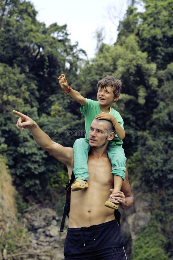 Πατέρας και γιος που κάνουν ένα ταξίδι στον καταρράκτη από κοινού στοκ εικόνες