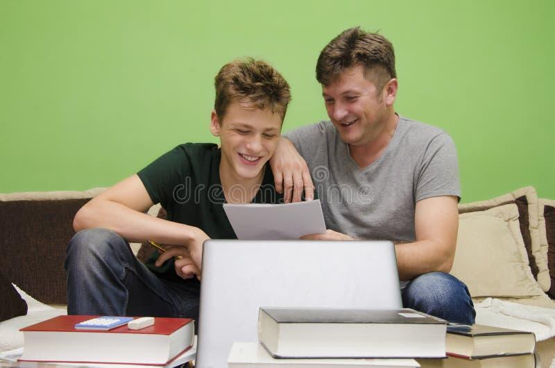 Πατέρας και γιος που κάνουν την εργασία από κοινού στοκ φωτογραφίες