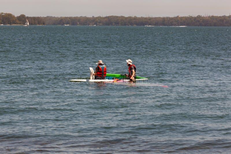 Πατέρας και γιος που κάνουν τις windsurfing επισκευές στο νερό για να πάει γρηγορότερα Σύνδεση πέρα από έναν αθλητικό ανταγωνισμό στοκ φωτογραφία με δικαίωμα ελεύθερης χρήσης
