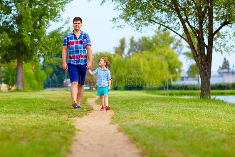 Πατέρας και γιος που περπατούν μαζί στο πάρκο στοκ εικόνες