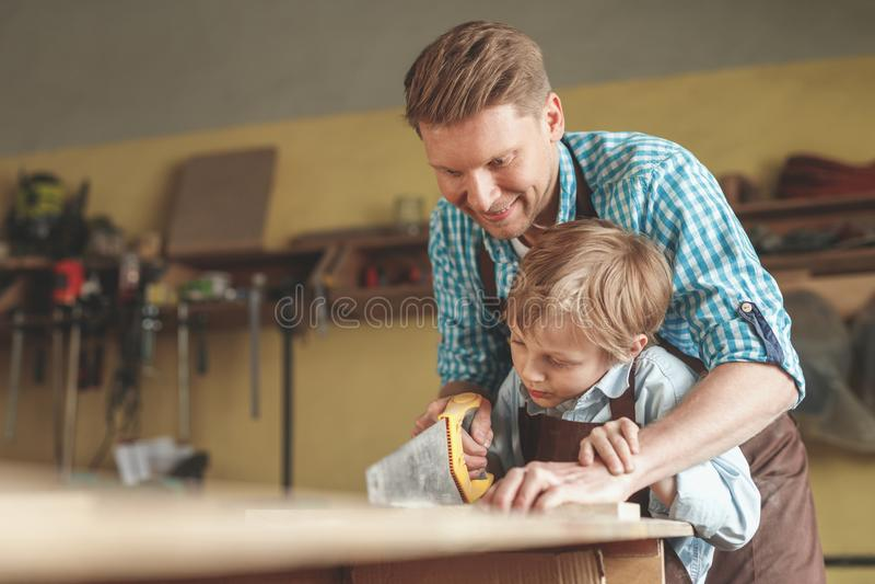 Πατέρας και γιος που πριονίζουν έναν πίνακα στο εσωτερικό στοκ φωτογραφία με δικαίωμα ελεύθερης χρήσης