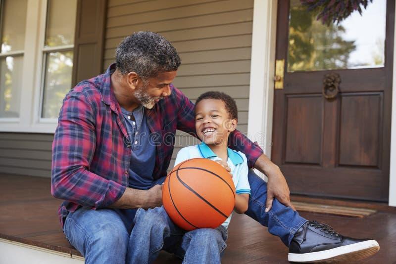 Πατέρας και γιος που συζητούν την καλαθοσφαίριση στο μέρος του σπιτιού στοκ εικόνες