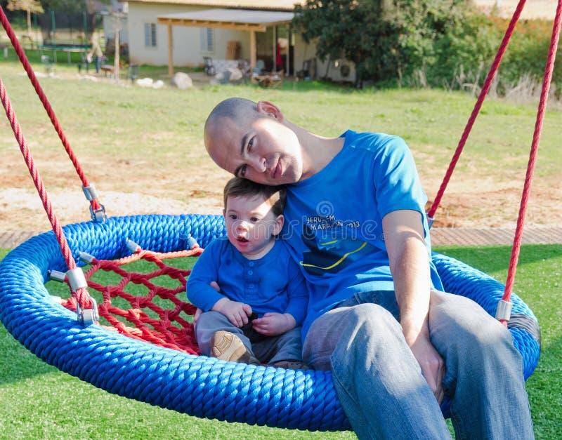 Πατέρας και γιος σε μια ταλάντευση στοκ φωτογραφίες