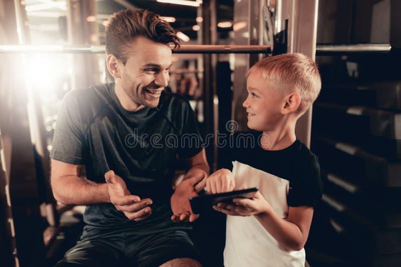 Πατέρας και γιος στη γυμναστική Πληροφορίες για την ταμπλέτα στοκ εικόνες με δικαίωμα ελεύθερης χρήσης