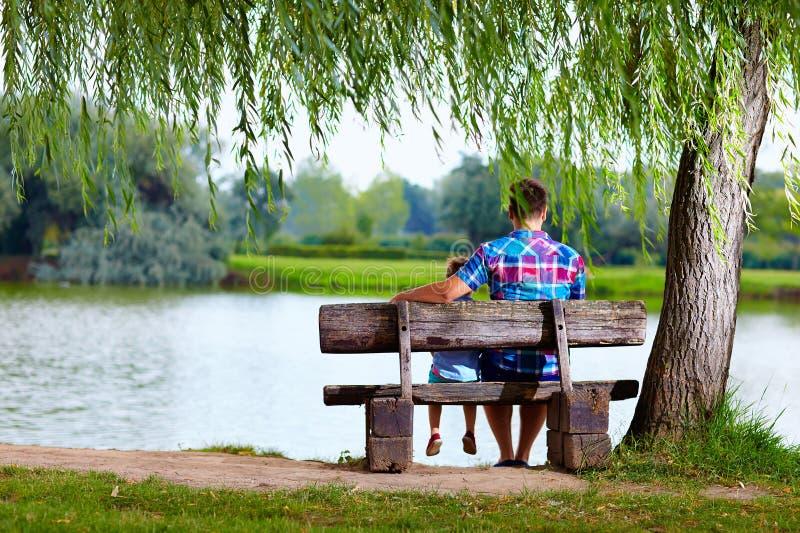 Πατέρας και γιος στον πάγκο κοντά στη λίμνη στοκ φωτογραφίες