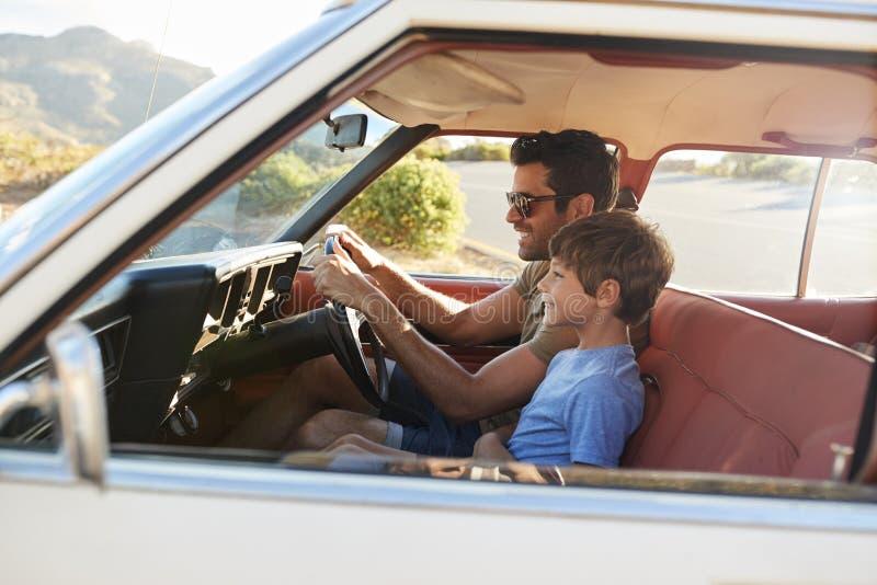 Πατέρας και γιος στο μπροστινό κάθισμα του αυτοκινήτου στο οδικό ταξίδι στοκ εικόνα