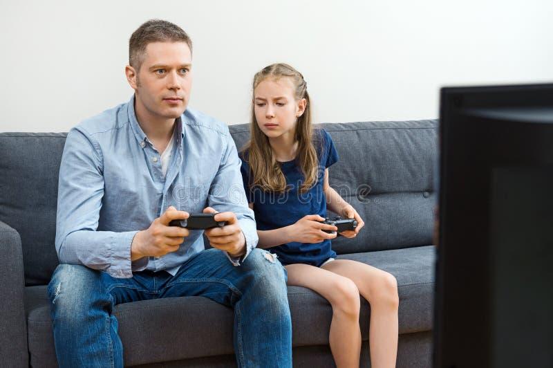 Πατέρας και κόρη που παίζουν το τηλεοπτικό παιχνίδι στοκ εικόνα με δικαίωμα ελεύθερης χρήσης