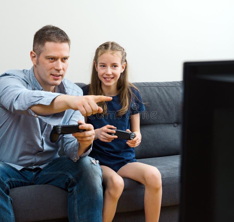 Πατέρας και κόρη που παίζουν το τηλεοπτικό παιχνίδι στοκ φωτογραφίες