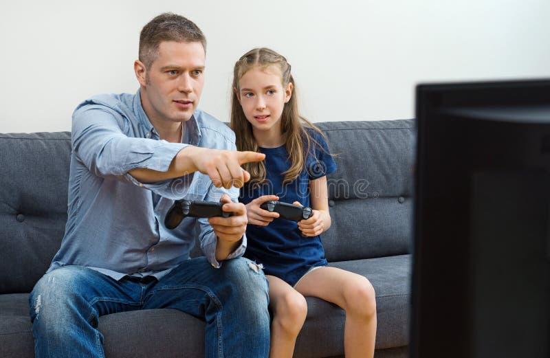 Πατέρας και κόρη που παίζουν το τηλεοπτικό παιχνίδι στοκ φωτογραφία με δικαίωμα ελεύθερης χρήσης
