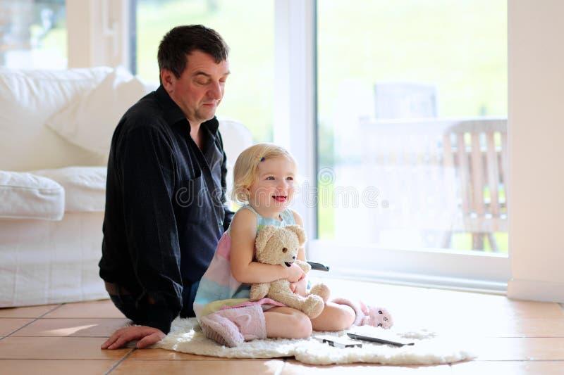 Πατέρας και κόρη που προσέχουν τη TV στο σπίτι στοκ εικόνες