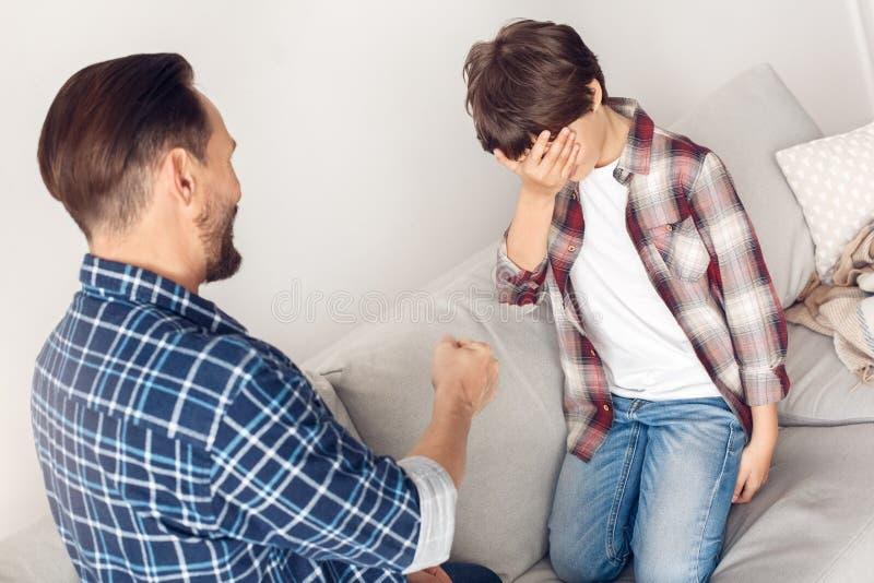 Πατέρας και λίγος γιος που κάθονται στο σπίτι στο παίζοντας rock†«paper†«αγόρι ψαλιδιού καναπέδων που χάνεται στοκ εικόνες