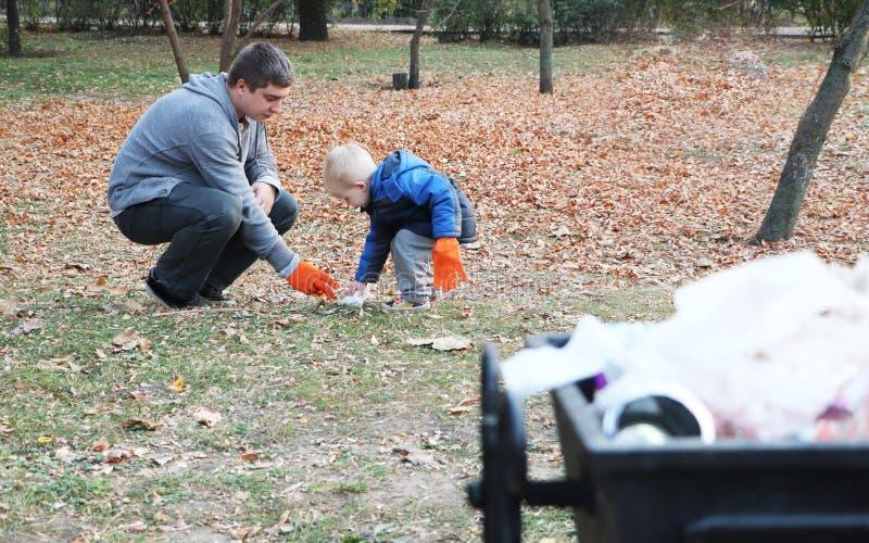 Πατέρας και λίγος γιος που σαρώνουν στο πάρκο Υπόβαθρο - δοχείο απορριμμάτων και απορριμάτων Η έννοια της οικολογίας και της προσ στοκ φωτογραφία με δικαίωμα ελεύθερης χρήσης