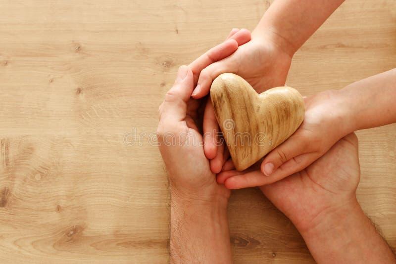 Πατέρας και λίγο παιδί που διατηρούν τη συνοχή την ξύλινη καρδιά Έννοια ημέρας του ευτυχούς πατέρα στοκ εικόνες με δικαίωμα ελεύθερης χρήσης