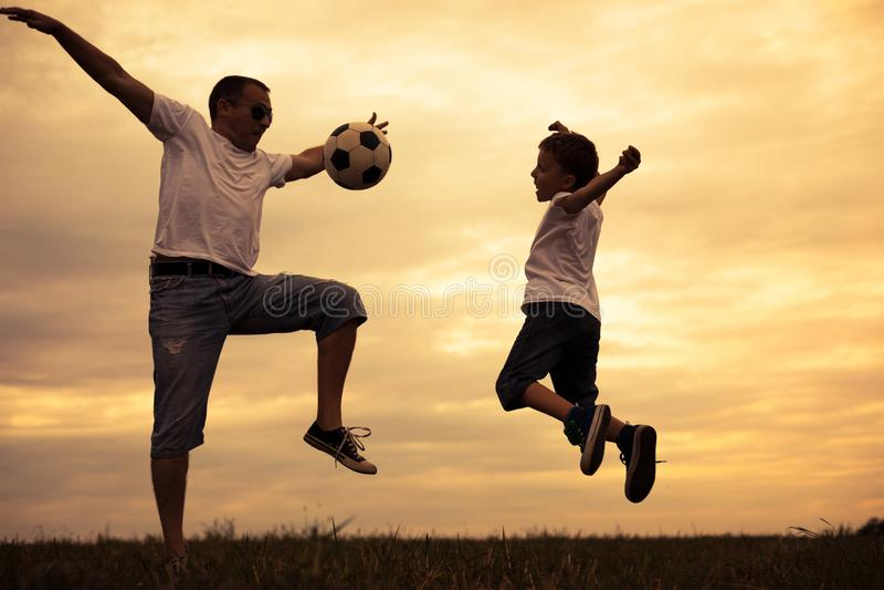 Πατέρας και νεολαίες λίγος γιος που παίζει στον τομέα με το BA ποδοσφαίρου στοκ εικόνες με δικαίωμα ελεύθερης χρήσης