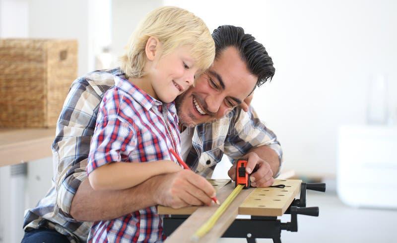 Πατέρας και ο γιος του που εργάζονται στην ξύλινη σανίδα στοκ φωτογραφία