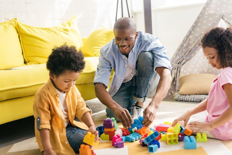 πατέρας και παιδιά αφροαμερικάνων που παίζουν με τους ζωηρόχρωμους φραγμούς στο πάτωμα από κοινού στοκ φωτογραφία με δικαίωμα ελεύθερης χρήσης